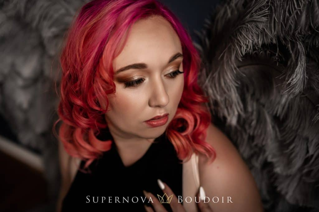 photo of a woman with hot pink hair wearing grey angel wings from leah maria couture