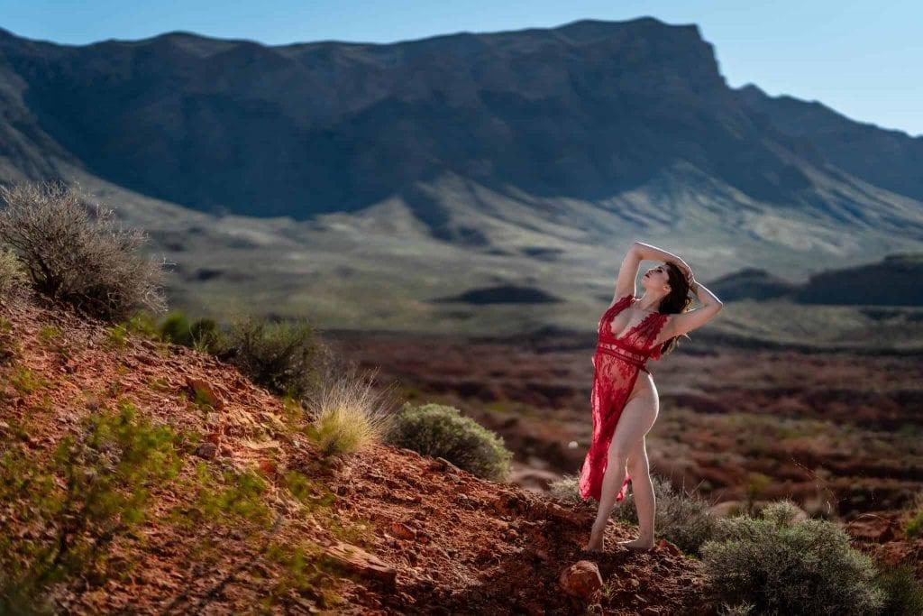 model in a red dress posing in red rocks park