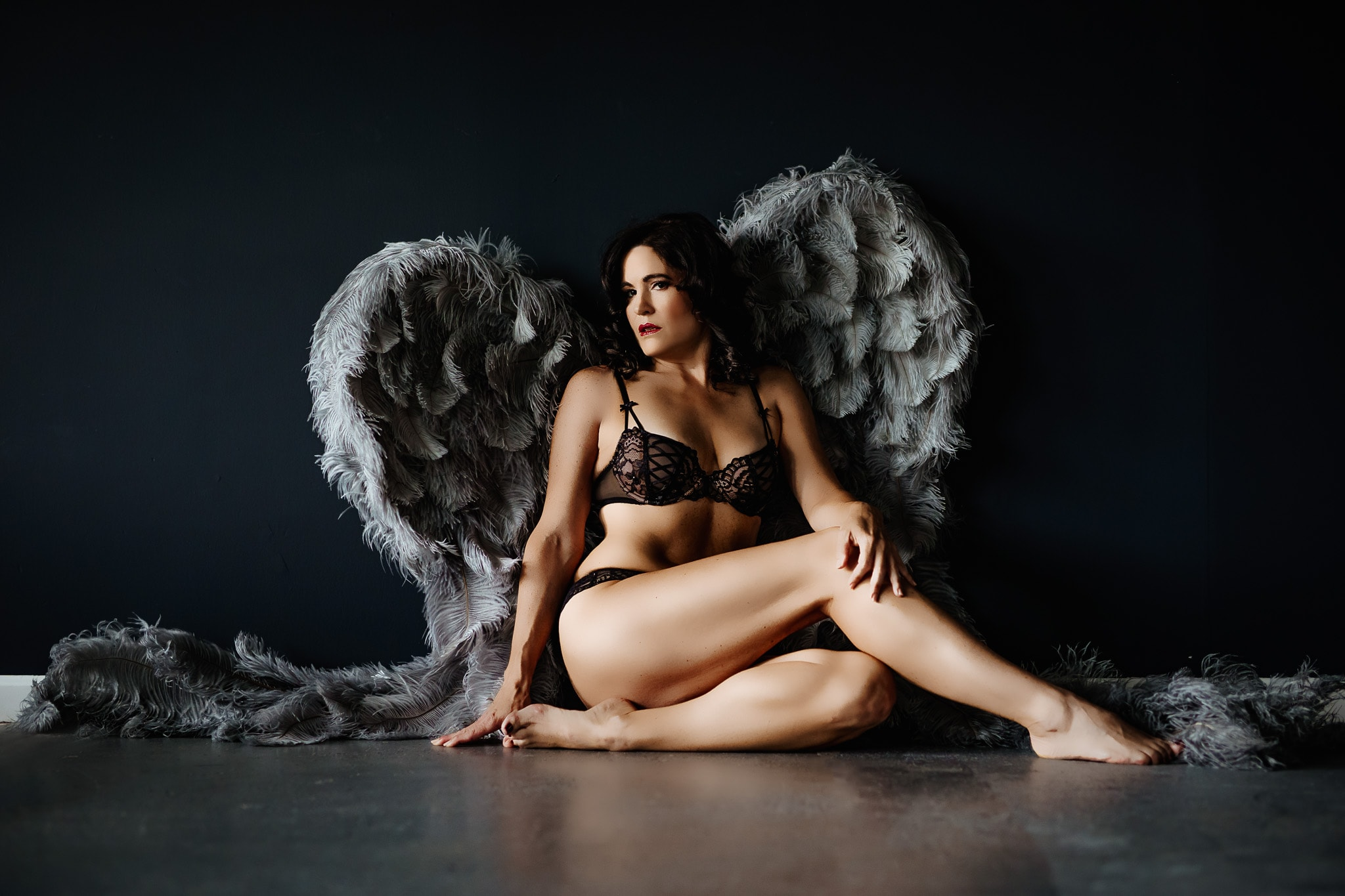 A 50 year old woman wearing angel wings in her boudoir session